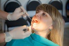 Tandläkare som kontrollerar en kvinna för hål royaltyfria foton