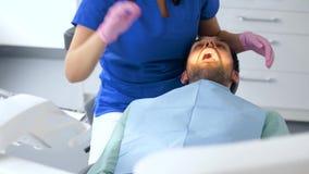 Tandläkare som kontrollerar tålmodiga tänder på den tand- kliniken arkivfilmer