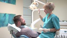 Tandläkare som kontrollerar upp tänder av patienten och talar med honom stock video