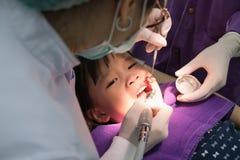 Tandläkare som polerar asiatiska flickatänder arkivbild