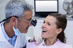 Tandläkare som undersöker en kvinnlig patient med tand- loupes Arkivbild