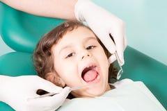 Tandläkare som undersöker liten girl& x27; s-tänder Royaltyfria Foton