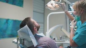 Tandläkare som undersöker tand för ` s för borrande en tålmodig Docka- och steadicamskott arkivfilmer