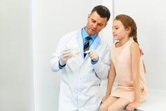 Tandläkare som visar en flicka hur man borstar hennes tänder Fotografering för Bildbyråer