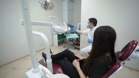 Tandläkaredoktor som kontrollerar tålmodiga tänder arkivfilmer