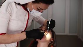 Tandläkarekontor, en ung kvinnlig tandläkare i den vita ämbetsdräkten och maskering som undersöker och arbetar på patienttänderna arkivfilmer