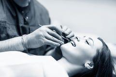 Tandläkarekontroll-upptänder till patienten för ung kvinna i klinik royaltyfri fotografi