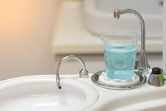 Tandläkarekopp eller exponeringsglasvatten för washmun och vask royaltyfria bilder
