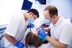 Tandläkaren behandlar tänder royaltyfri foto