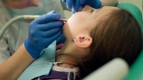 Tandläkaren borrar en tandliten flicka arkivfilmer