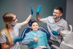 Tandläkaren för den unga mannen och kvinnager högt-fem till varandra i rum De ler Flickan sitter i tand- stol och rymmer stort royaltyfri fotografi