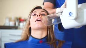 Tandläkaren gör röntgenstrålar för att en ung flicka ska bestämma den tålmodiga framtidsbehandlingen för ` s stock video