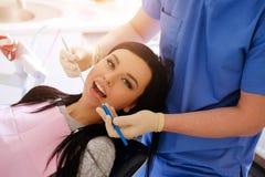 Tandläkaren i blåa enhetliga och vita handskar att bry sig på en caucasian kvinna för sexig brunett, ställning bak henne Royaltyfri Fotografi