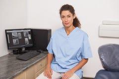 Tandläkaren i blått skurar att se kamerasammanträde på skrivbordet royaltyfri foto