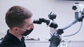 Tandläkaren kontrollerar närbilden för den optiska apparaten lager videofilmer