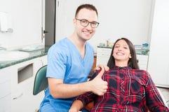 Tandläkaren med hans tålmodiga le visning tummar upp Arkivfoto