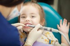 Tandläkaren polerar childständer med det moderna elektriska hjälpmedlet royaltyfri foto