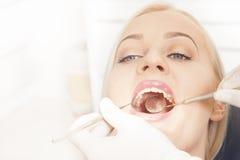 Tandläkaren räcker arbete med kvinnliga tänder royaltyfri bild