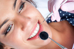 Tandläkaren räcker arbete på kvinnliga tänder arkivfoto