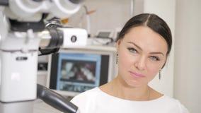 Tandläkaren riktar det moderna mikroskopet till patienten Härlig Young African American för kvinnadoktorstandläkare man stock video
