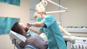Tandläkaren sitter ner och undersökande tänder av patienten Glidareskott som är högert stock video