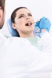 Tandläkaren undersöker det muntliga hålet av tålmodign Royaltyfri Bild