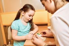 Tandläkaren visar lite flickan hur man gör ren tandprotesen arkivfoton