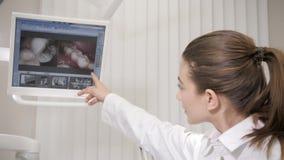 Tandläkaren visar röntgenstrålar till patienten Stående som charmar den härliga flickadoktorstandläkaren i tand- klinik Medicin lager videofilmer
