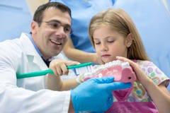 Tandläkareundervisningflicka hur man borstar riktigt hennes tänder arkivbilder