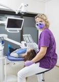 TandläkareWearing Loupes While undersökande patient i klinik Arkivbild