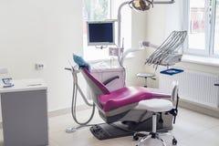 Tandläkekonstinsida, violett stol för patient och utrustning fotografering för bildbyråer