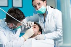 Tandläkekonstutbildning Manlig tandläkaredoktorslärare som förklarar behandlingtillvägagångssätt royaltyfri bild