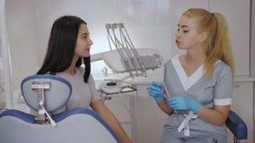 Tandl?kare och patient som v?ljer behandling i en konsultation med medicinsk utrustning i bakgrunden lager videofilmer