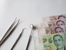 tandl?kareredskap f?r muntlig granskning och singaporean sedlar royaltyfri foto