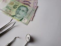 tandl?kareredskap f?r muntlig granskning och singaporean sedlar arkivfoton