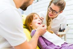 Tandläkare som ger flickabehandling Fotografering för Bildbyråer
