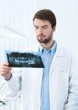 Tandläkaren tänker över roentgenogramen Arkivbild