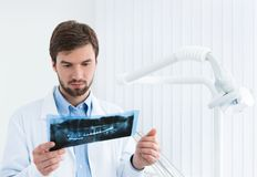 Tandläkaren undersöker roentgenogramen Fotografering för Bildbyråer