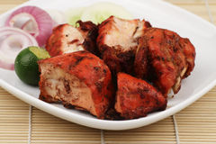 Tandoori Chicken. A plate of chopped Tandoori Chicken with some garnishing on a bamboo mat Royalty Free Stock Images