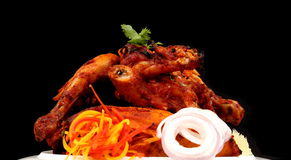 TANDOORI CHICKEN. Tandoor is a clay oven in which the spice and yogurt marinated chicken or meat is grilled and the chicken prepared in tandoori is a dish Royalty Free Stock Photo