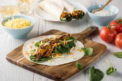 Tandoori chicken wrap with tzatziki. Fresh healthy chargrilled tandoori chicken wrap with tzatziki, cheese, baby spinach and carrots Stock Photography
