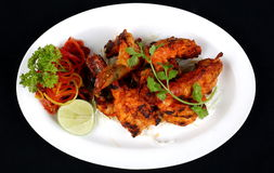 TANDOORI PRAWN. A tandoor is a cross between a barbecue pit and an oven. The waist-high, urn-shaped clay vessel holds a charcoal fire in the bottom. Seafood Stock Images