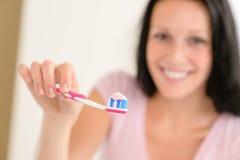 Tandpasta bij de tanden van de tandenborstelclose-up het borstelen Stock Fotografie
