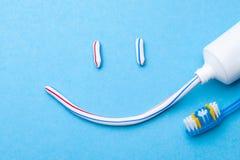 Tandpasta in de vorm van een gezicht met een glimlach Buis van tandpasta en tandenborstel op een blauwe achtergrond stock afbeeldingen