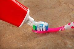 Tandpasta en tandenborstel op bruine achtergrond Royalty-vrije Stock Foto's