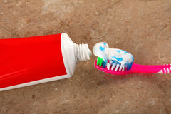 Tandpasta en tandenborstel op bruine achtergrond Stock Afbeelding