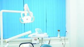 Tandstoel en andere die toebehoren door tandartsen in blauw, dokterslicht, geneeskundeconcept wordt gebruikt Modern tandmateriaal stock videobeelden