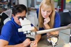 Tandtechnici die aan microscoop werken stock afbeelding