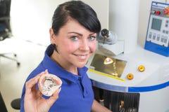 Technicus in een tandlaboratorium die een prothese voorstellen in de camera stock afbeelding