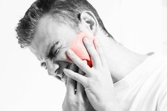 Tandvärk medicin, hälsovårdbegreppet, tandproblem, lidande för den unga mannen från tanden smärtar, karies, i en vit t-skjorta på Royaltyfri Foto